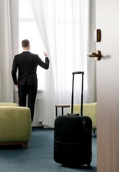 Vista traseira do empresário vestindo um terno escuro em pé no quarto do hotel, olhando pela janela