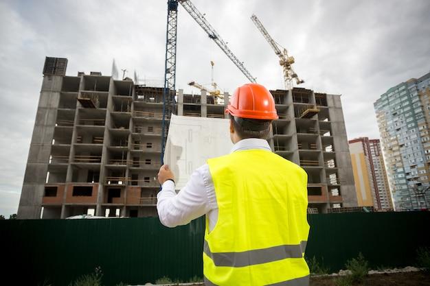 Vista traseira do engenheiro de construção, olhando para a planta do prédio