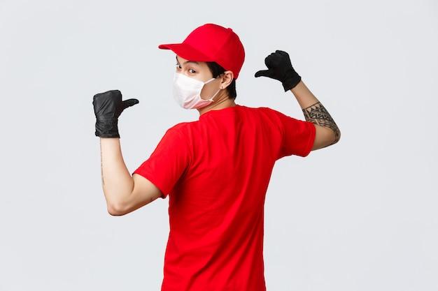 Vista traseira do entregador asiático em máscara médica e luvas de proteção, use gorro vermelho, camiseta, vire para a câmera, apontando para trás para mostrar o logotipo da empresa em uniforme.