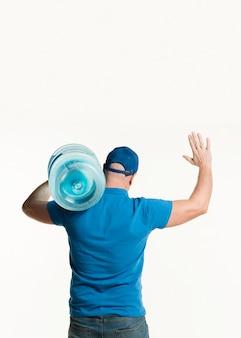 Vista traseira do entregador segurando a garrafa de água