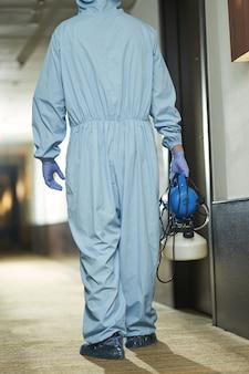 Vista traseira do especialista masculino em terno azul com desinfetante para higienizar o quarto no hotel. coronavírus e conceito de quarentena