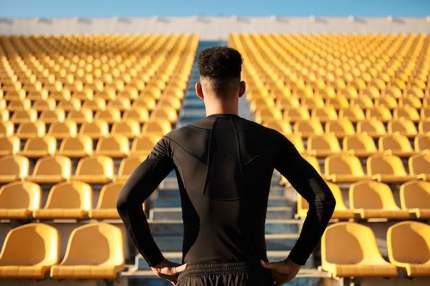 Vista traseira do esportista entre assentos do estádio vazio