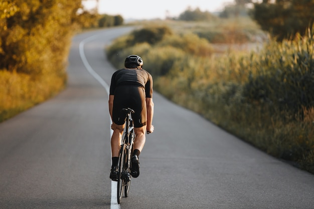Vista traseira do esportista praticando ciclismo na natureza