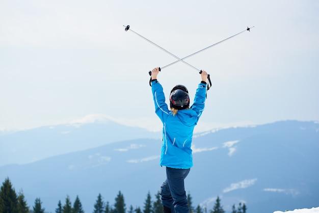 Vista traseira do esquiador de mulher segurando postes acima de uma cabeça, desfrutando de esqui na estância de esqui nas montanhas