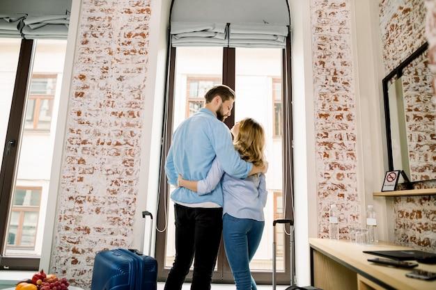 Vista traseira do feliz casal apaixonado no quarto de hotel, abraçando e de pé na janela