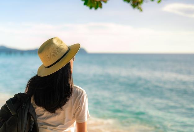 Vista traseira do feliz jovem asiática na moda estilo casual com chapéu de palha e mochila. relaxe e aproveite as férias na praia paradisíaca tropical. vibes do verão.