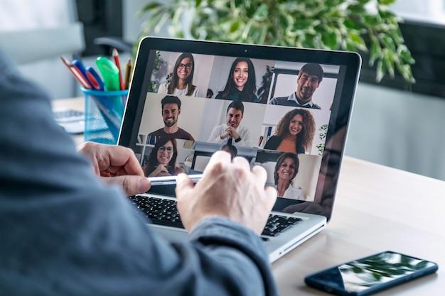 Vista traseira do funcionário do sexo masculino falando em videochamada com diversos colegas no briefing on-line com o laptop em casa.