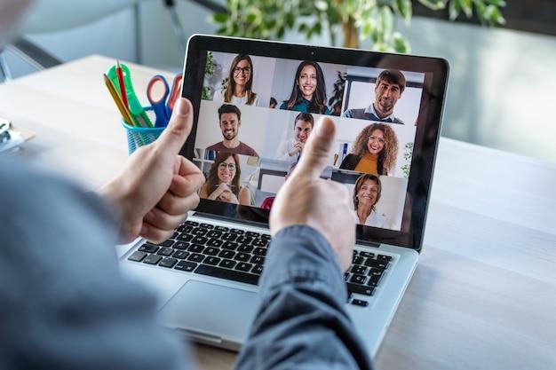Vista traseira do funcionário fazendo uma aprovação gesticulando com o polegar enquanto fala em videochamada com diversos colegas em briefing online com laptop em casa.