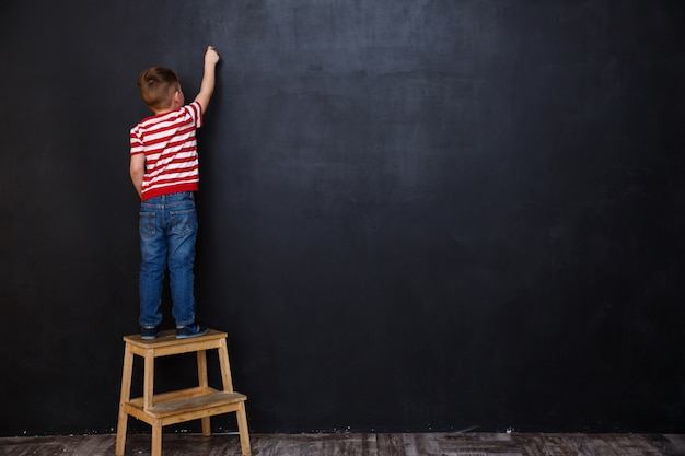 Vista traseira do garoto garoto bonitinho escrevendo com giz