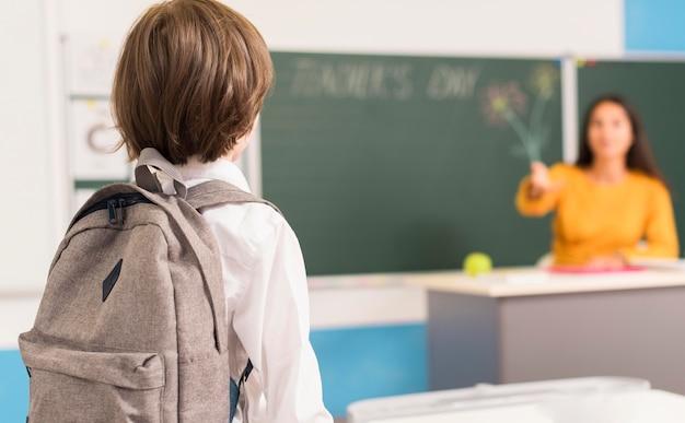 Vista traseira do garoto olhando para o professor