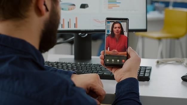 Vista traseira do gerente de projeto segurando smartphone ouvindo empresa líder remota em videochamada, falando online usando fones de ouvido, discutindo em reunião virtual sobre estatística explicativa de projeto financeiro