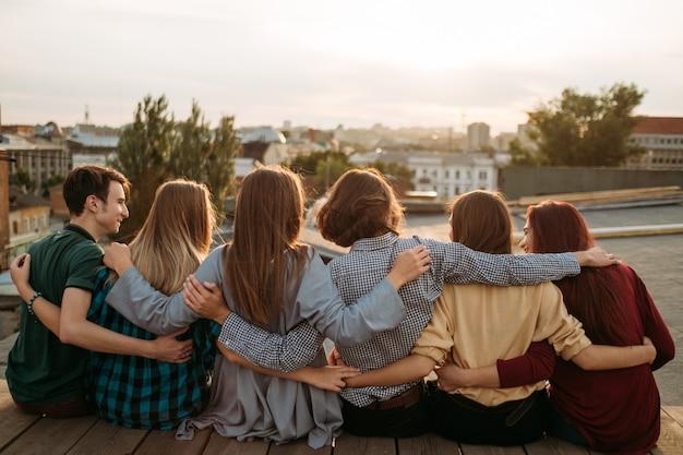 Vista traseira do grupo de amigos. arme-se. suporte da unidade. amizade juventude união lazer diversidade