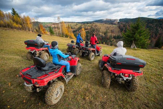 Vista traseira do grupo de cinco pessoas andando de bicicleta quad na colina e apreciando a bela paisagem de outono
