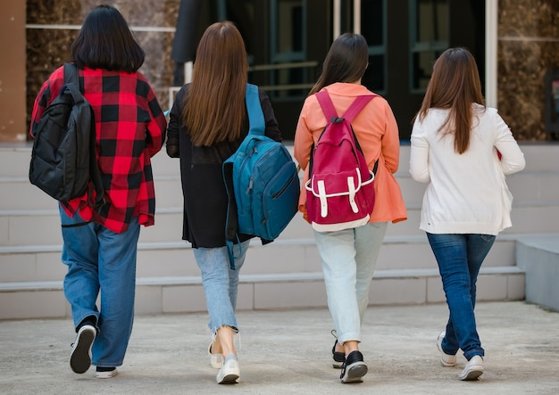 Vista traseira do grupo de quatro jovens garotas asiáticas atraentes estudantes universitários caminhando juntos no campus da universidade. conceito de educação, amizade e vida de estudantes universitários.