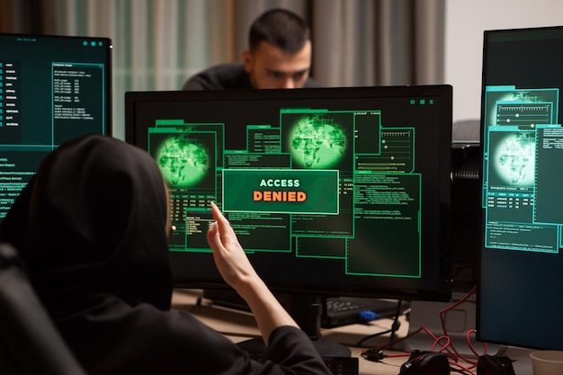 Vista traseira do hacker feminino com raiva após acesso negado, mostrando na área de trabalho do computador.