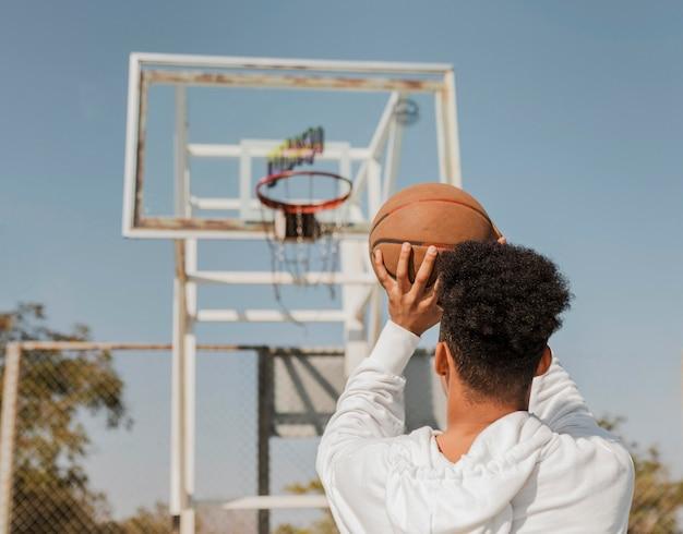 Vista traseira do homem afro-americano jogando basquete do lado de fora