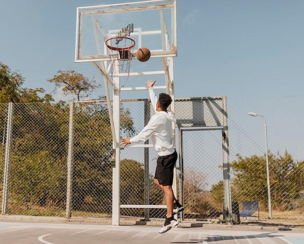 Vista traseira do homem afro-americano jogando basquete