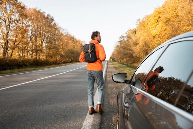 Vista traseira do homem ao lado do carro durante uma viagem