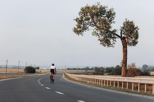 Vista traseira do homem ativo com roupa esportiva andando de bicicleta no meio de uma estrada de asfalto