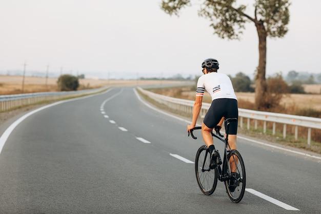 Vista traseira do homem ativo em uma camiseta branca, calção preto e capacete protetor em bicicleta ao ar livre