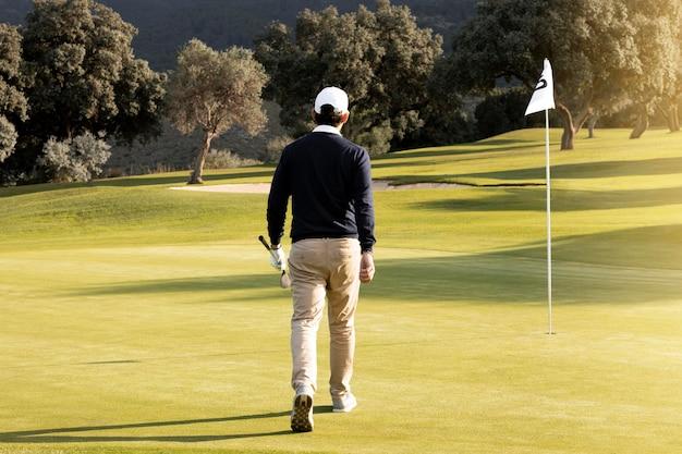 Vista traseira do homem caminhando em direção à bandeira no campo de golfe
