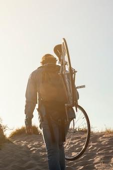 Vista traseira do homem carregando bicicleta