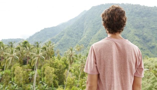 Vista traseira do homem caucasiano em t-shirt em pé ao ar livre na frente da floresta tropical e contemplando belezas da natureza selvagem exótica em dia ensolarado. turista apreciando a bela paisagem durante a viagem de trekking