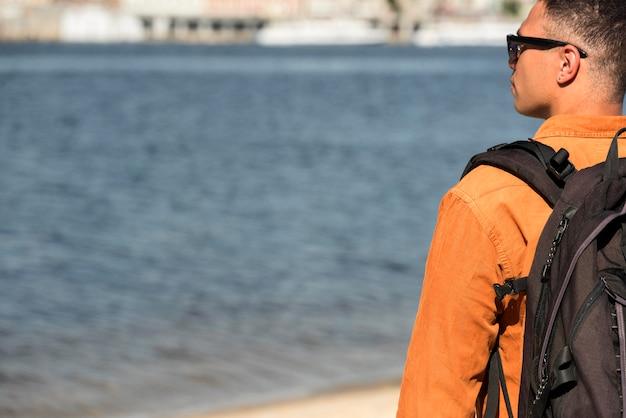 Vista traseira do homem com mochila na praia