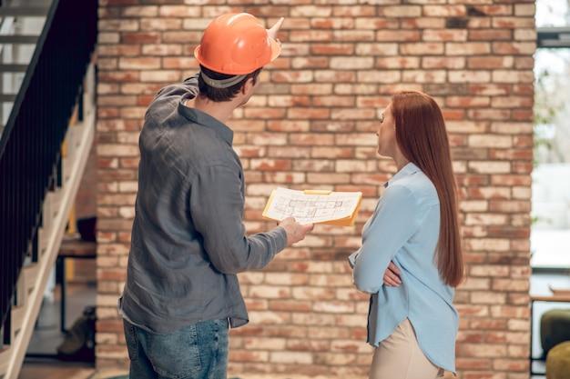 Vista traseira do homem com plano de construção e mulher