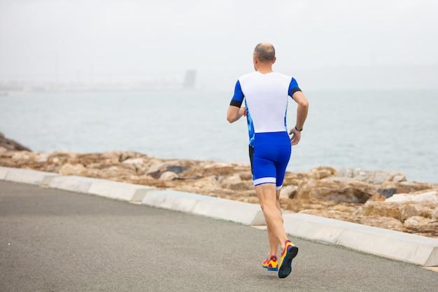 Vista traseira do homem correndo na costa do mar