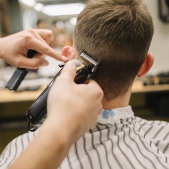 Vista traseira do homem cortando o cabelo