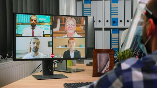 Vista traseira do homem de negócios em cadeira de rodas, falando com colegas sobre o plano em videoconferência, usando viseira no novo escritório normal. freelancer imobilizado trabalhando em empresa que respeita a distância social