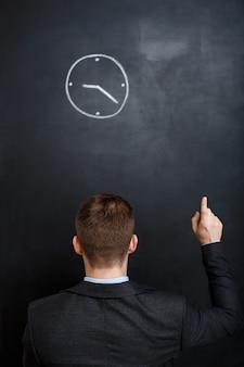 Vista traseira do homem de negócios, olhando para o ponto do relógio com um dedo
