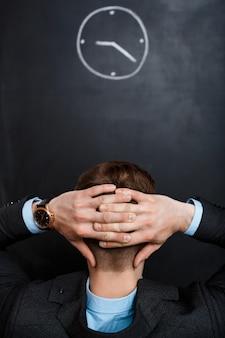 Vista traseira do homem de negócios, olhando para os ponteiros do relógio atrás dele hea