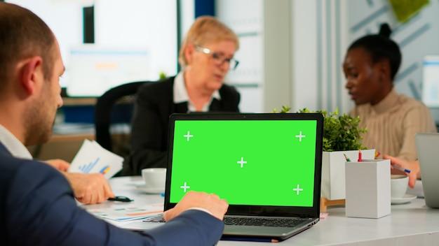 Vista traseira do homem de negócios sentado na mesa de conferência usando laptop com tela verde, falando com o colega enquanto a equipe trabalha no fundo. colegas de trabalho multiétnicas planejando projeto no display chroma key