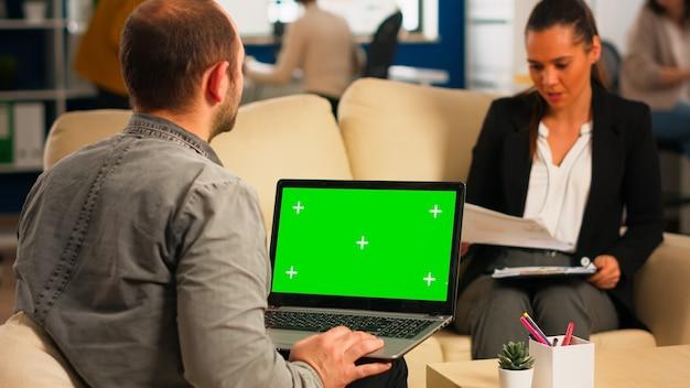 Vista traseira do homem de negócios, sentado no sofá, usando o laptop com tela verde, falando com o colega enquanto a equipe trabalha no fundo. colegas de trabalho multiétnicas planejando projeto no display chroma key