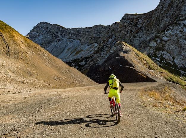 Vista traseira do homem do esporte ativo andando de bicicleta de montanha no cume