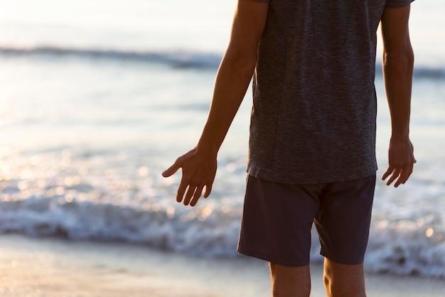 Vista traseira do homem em pé próximo ao mar