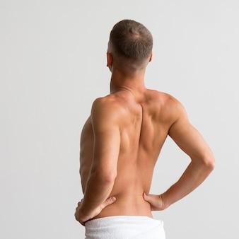Vista traseira do homem em uma toalha posando sem camisa