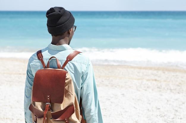 Vista traseira do homem europeu preto carregando mochila de couro marrom em pé na praia deserta sozinho, de frente para o mar azul, chegou à praia