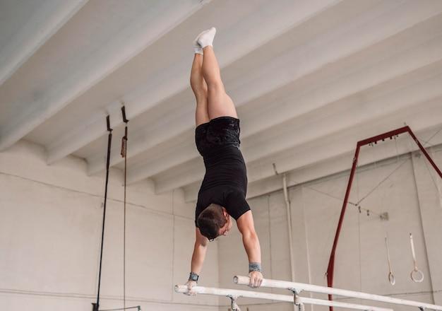 Vista traseira do homem fazendo exercícios nas barras paralelas