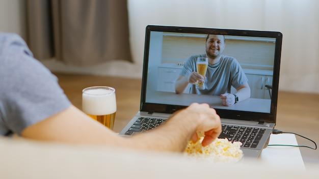 Vista traseira do homem feliz na chamada de vídeo com seu amigo bebendo cerveja durante o isolamento do coronavírus.