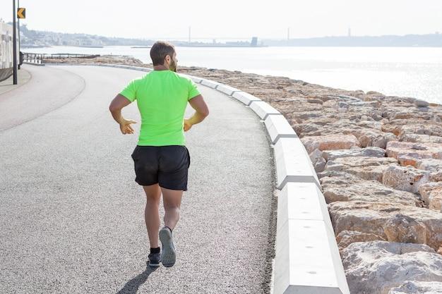 Vista traseira do homem forte que corre na estrada pelo mar