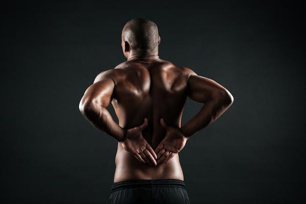 Vista traseira do homem jovem esportes africanos, sentindo dor nas costas