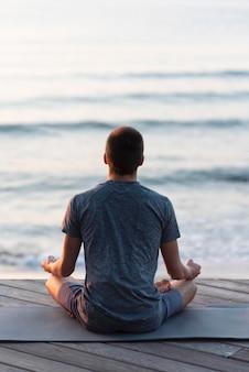 Vista traseira do homem meditando em lótus
