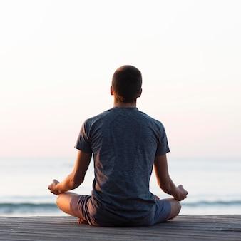Vista traseira do homem meditando na praia
