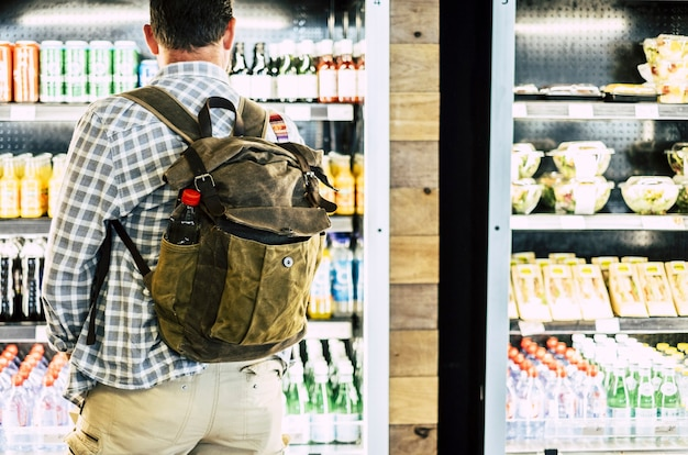 Vista traseira do homem na mochila em pé contra a loja de bebidas geladas. homem escolhendo a bebida no supermercado. atrás de um cliente do sexo masculino comprando bebidas em uma loja de departamentos