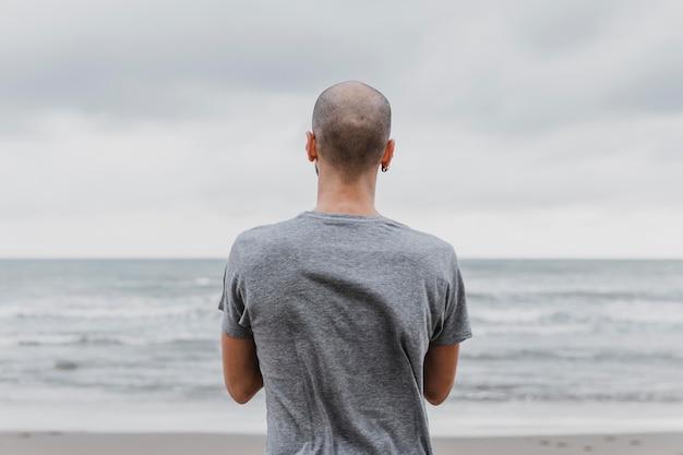 Vista traseira do homem na praia praticando ioga