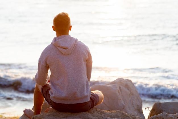 Vista traseira do homem relaxando na praia com espaço de cópia