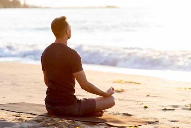 Vista traseira do homem relaxando na praia do lado de fora